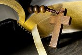 stock photo of prayer beads  - Wooden rosary with cross in front of holy bible - JPG