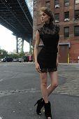 Woman wearing black minidress standing under Manhattan Bridge