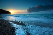 stock photo of atlantic ocean beach  - sunset over stone beach in Atlantic ocean Etretat France - JPG