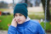 Sorrowful teenage boy swinging in the park