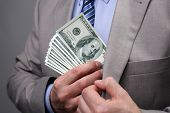 stock photo of white collar crime  - Man putting money in suit jacket pocket concept for corruption - JPG