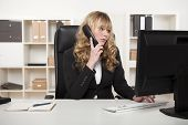 Businesswoman Talking On The Phone While Typing