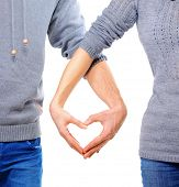 Valentine Couple in love showing Heart with their fingers. Love Concept. Valentines Day. Family with Heart made by their Hands. Young Man and Woman. Love Concept. Heart Sign. Valentines Day