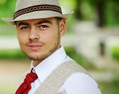 Young stylish man wearing hat shirt and tie in sunny day