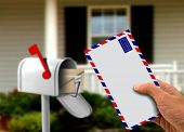 Hand Holding Envelope In Front Of A House