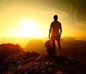 Hiker standing with backpack on top of a mountain and enjoying sunrise