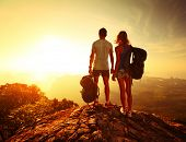 stock photo of breathtaking  - Hikers with backpacks relaxing on top of a mountain and enjoying valley view - JPG
