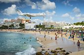 PHILIPSBURG, SINT MAARTEN - DECEMBER 30, 2013: A commercial jet approaches Princess Juliana airport above onlooking spectators. The short runway gives beach goers close proximity views of the planes.