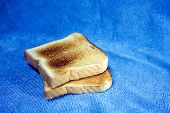 Two Pieces Of Toast On Blue Background