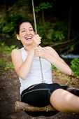 pic of seesaw  - Young woman swinging on seesaw outdoor in nature - JPG
