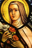 LOS ANGELES, CA, USA - NOVEMBER 27, 2013: Illustrative photo of a beautiful vibrant stained glass depicting nun holding crucifix and roses.
