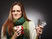 Woman Holding A Cup Of Hot Tea And Expressing Disgust To Some Blister Packed Tablets She Is Holding