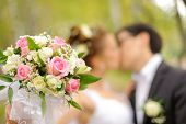 Wedding shot of bride and groom kiss in park (focus on bouquet)