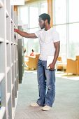 Full length of male student with digital tablet selecting book in bookstore