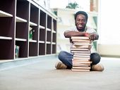 Full length portrait of happy African American student leaning on stacked books while sitting on flo