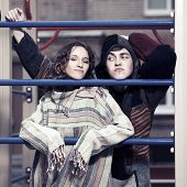stock photo of hippy  - Young hippie man and woman on the children playground - JPG