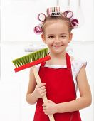Little housekeeping fairy girl with large hair curls holding broom