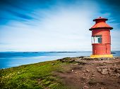 Little red lighthouse situated at the top of a cape over a sunny seascape. Related concept: navigati