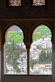 GRANADA, SPAIN - MARCH 11, 2013: View of Granaga through window of Alhambra palace - masterpiece of