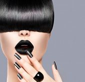 High Fashion Model Girl Portrait with Trendy Hair style, Black Make up and Manicure. Long Black Glossy Fringe Hairstyle, Black Matte Nail Polish and Lipstick. Woman Makeup. Haircut