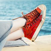 Red Fashion Sneakers On Girl And Sea Landscape
