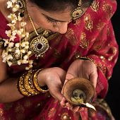 Beautiful Indian female hands holding diya oil lamp, celebrating diwali festive of lights, traditional sari prayer isolated on black background with copy space on side.