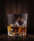 Glasses of whiskey on wood background