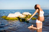 image of pregnancy exercises  - Pregnant woman in sports bra doing exercise in relaxation on yoga pose on sea - JPG