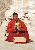 LHASA, TIBET - CIRCA MARCH 2008: Unknown buddhist monk sits on the ground and prays in the streets of Lhasa circa March 2008 in Tibet, China.