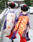 Two Geisha Walking On A Bridge In Arashiyama, Japan