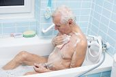 stock photo of bath sponge  - Senior man washing his body with soap sponge in bath - JPG