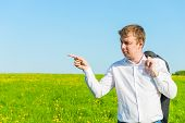 Young Businessman In A Field Indicates The Side