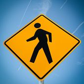 crosswalk sign with a man walking on yellow with a blue sky background