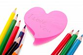 Colored Pencils And A Sheet Of Paper In The Shape Of A Heart With The Words I Love You