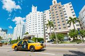 MIAMI,USA - MAY 20,2014 : Famous art deco hotels and traffic  at Collins Avenue on a sunny day at Miami Beach