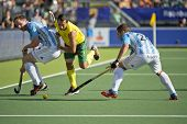 THE HAGUE, NETHERLANDS - JUNE 13: Australian star player Jamie Dwyer rushes past two Argentinian defenders during the semi-finals at the World Championships Hockey in 2014