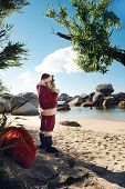 Santa Claus standing on a beach taking a picture of the view