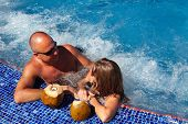 stock photo of hot-tub  - Romantic couple with coconut drink relaxing in hot tub - JPG