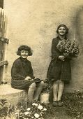 GERMANY, CIRCA 1930:  Vintage photo of two little girls with flowers