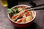 Chinese noodles with vegetables and seafood in bowl and wok on wooden background