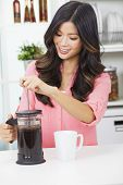 Beautiful young Asian Chinese woman or girl at home in her kitchen smiling and making a cup or mug of coffee with a french press or cafetiere