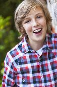 Young happy laughing boy outside wearing a checked plaid shirt