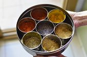 A typical indian spice box with multiple containers. Close up of a hand holding container.
