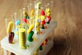 Different color drugs in test tubes, on wooden table background