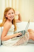 Cute girl smiling and looking at laptop. Home.