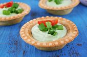Tartlets with greens and vegetables with sauce on table close-up