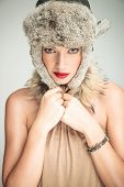 Young beautiful woman pulling her fur hat on while looking at the camera