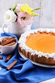 Composition of homemade pumpkin pie on plate and flowers in vase on wooden background