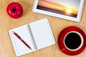 Tablet pc cup of coffee and notepad at table