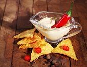 Tasty nachos and bowl with sauce on wooden background